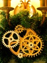 Photo of ornament made from cardboard gears hanging from a wall candle sconce with greenery