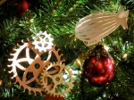 Closeup of Christmas tree ornaments, a gear cluster, a paper airship cutout, and an ordinary glass ball.