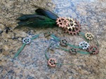 Fascinator made with green feathers, gears, and trailing ribbons strung with mini gears