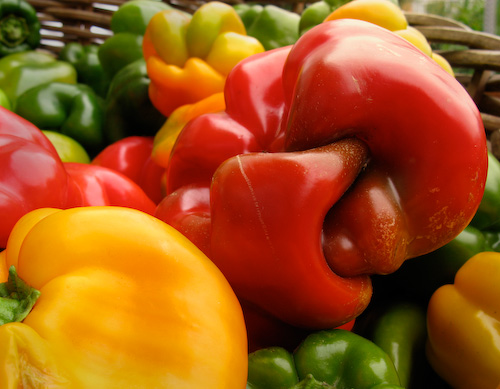 Twisted red bell pepper in a basket with other peppers